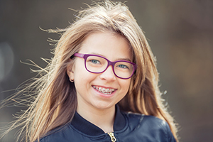 Young child smiling with metal braces after visit to orthodontist in Salem, OR